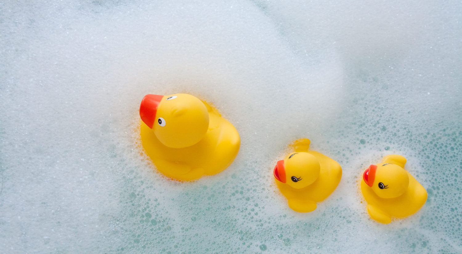 baby bath time tips Yellow rubber duckies swimming in bubbles at bath time
