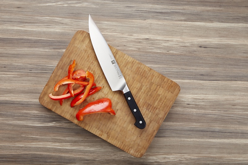 "9"" chef's knife on cutting board next to cut peppers"