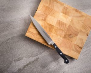"6"" utility knife resting on a cutting board"