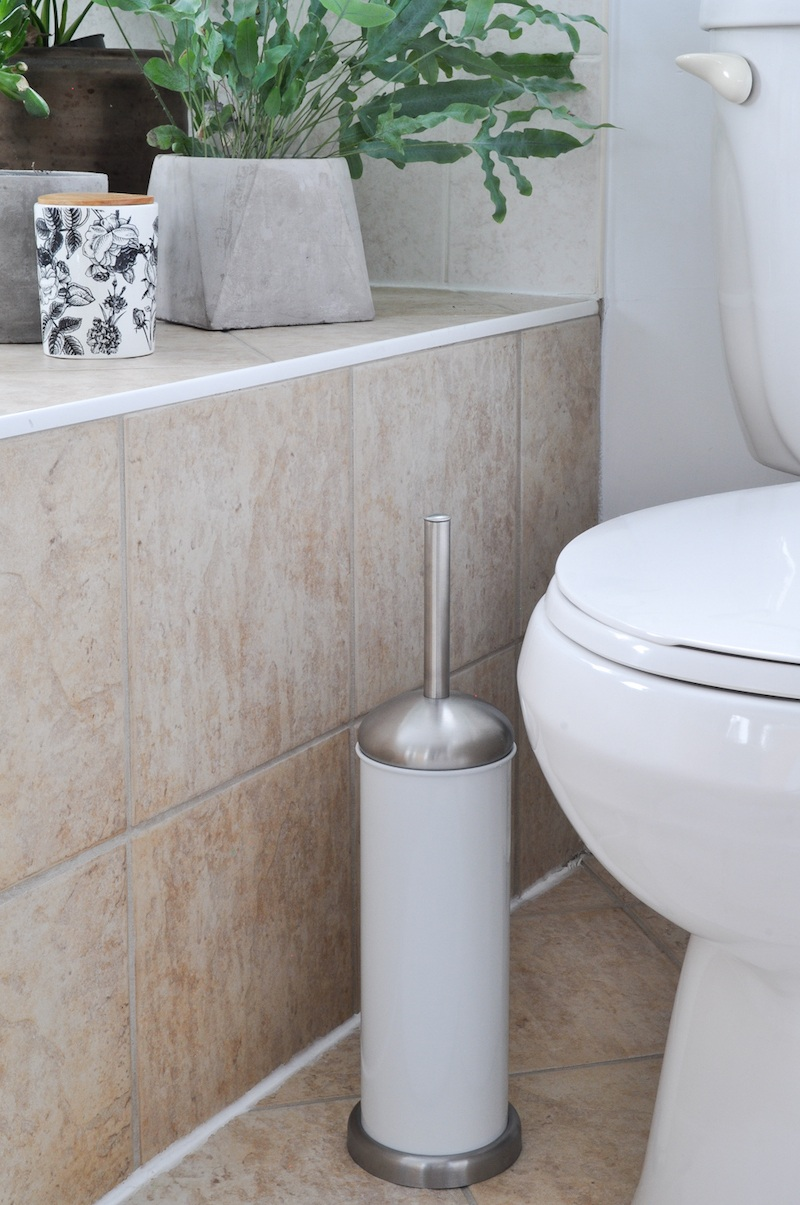 white toilet brush holder beside a toilet