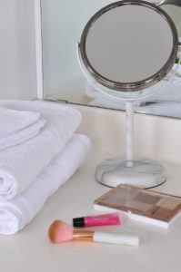 marble mirror beside glass canisters