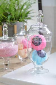 glass apothecary jars with bath bombs and bath salts