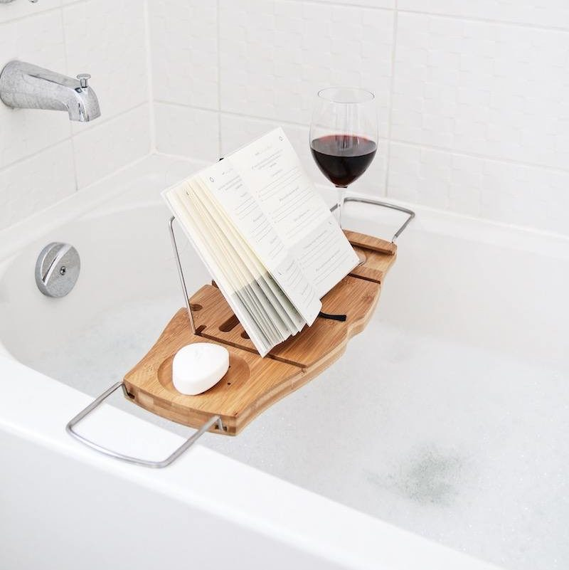 natural wood bathtub caddy with a glass of red wine and an open book