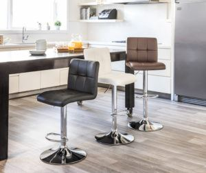 Wood kitchen island with three barstools in balck, white and brown.