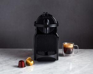 black nespresso inissia espresso maker beside an espresso