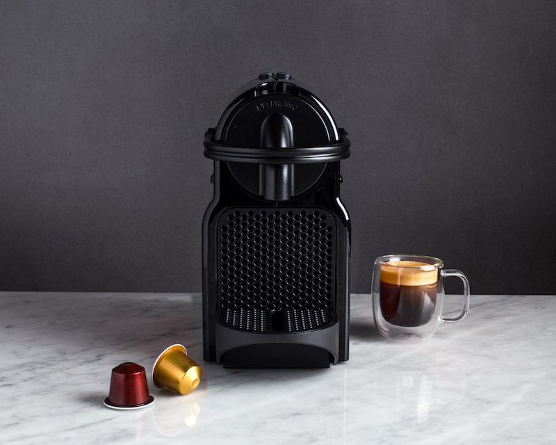 black inissia espresso maker beside an espresso