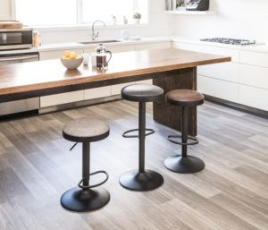 Wood kitchen island with three barstools in taupe, grey and brown.
