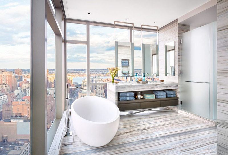 Bathrrom with floating white tub, modern grey tiles and floor to ceiling windows of New York City.