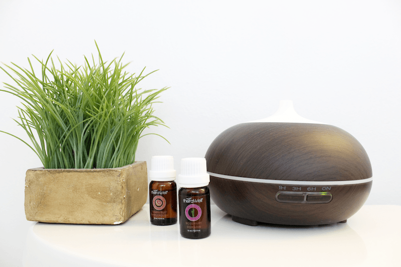 dark brown diffusers beside a green plant and bottles of lavender essential oil