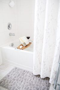 marble shower curtain half open with wooden bathtub caddy across tub