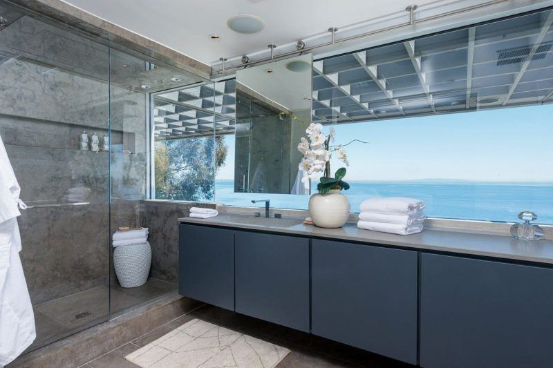 Glass encased shower, grey cabinetry with large view of the Malibu coastline.