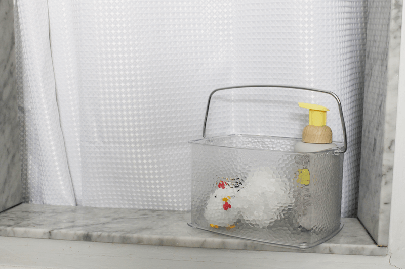 clear acrylic basket filled with children's bath toys