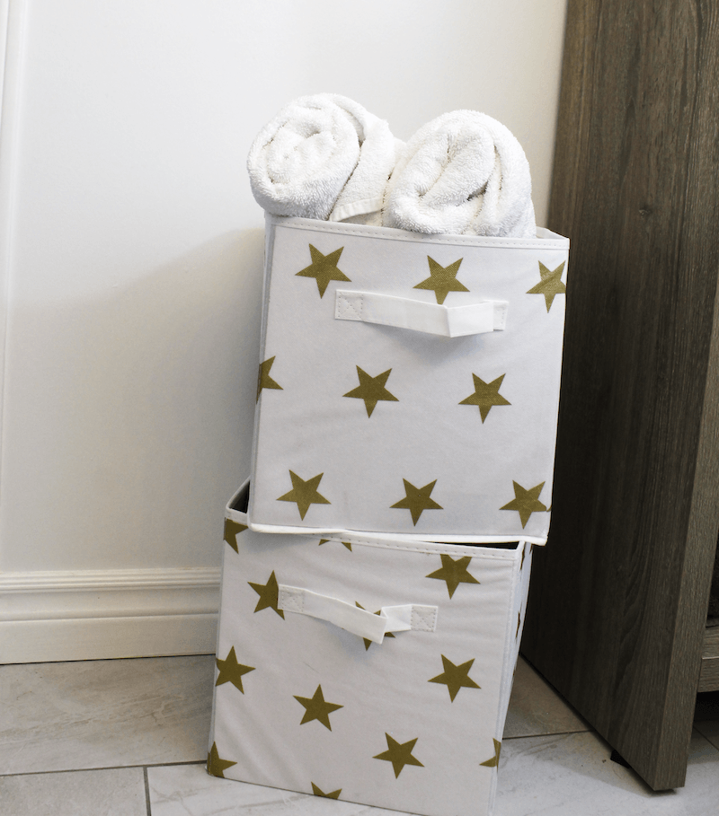 collapsible white storage bin with gold stars with white towels rolled up inside