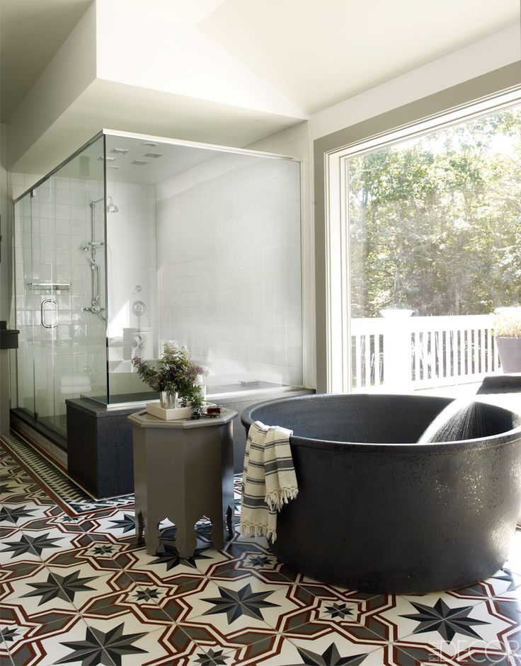 Hand painted tiles, circle stone tub and glass encased shower.