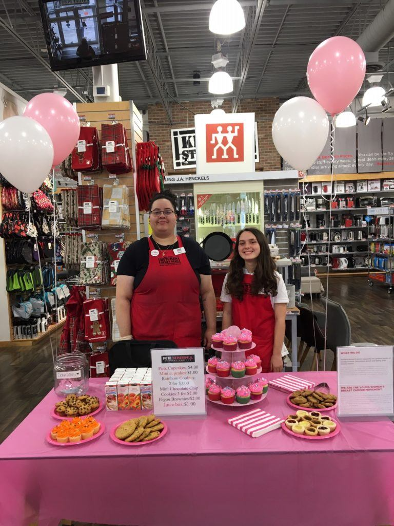 employees at the liberty village location standing behind our bake sale table for rethink breast cancer