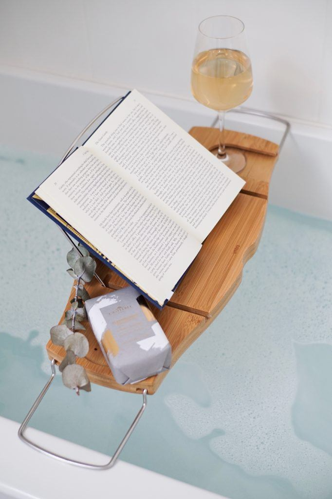 wooden bath caddy over a full bathtub with bubbles glass of white and open book on caddy