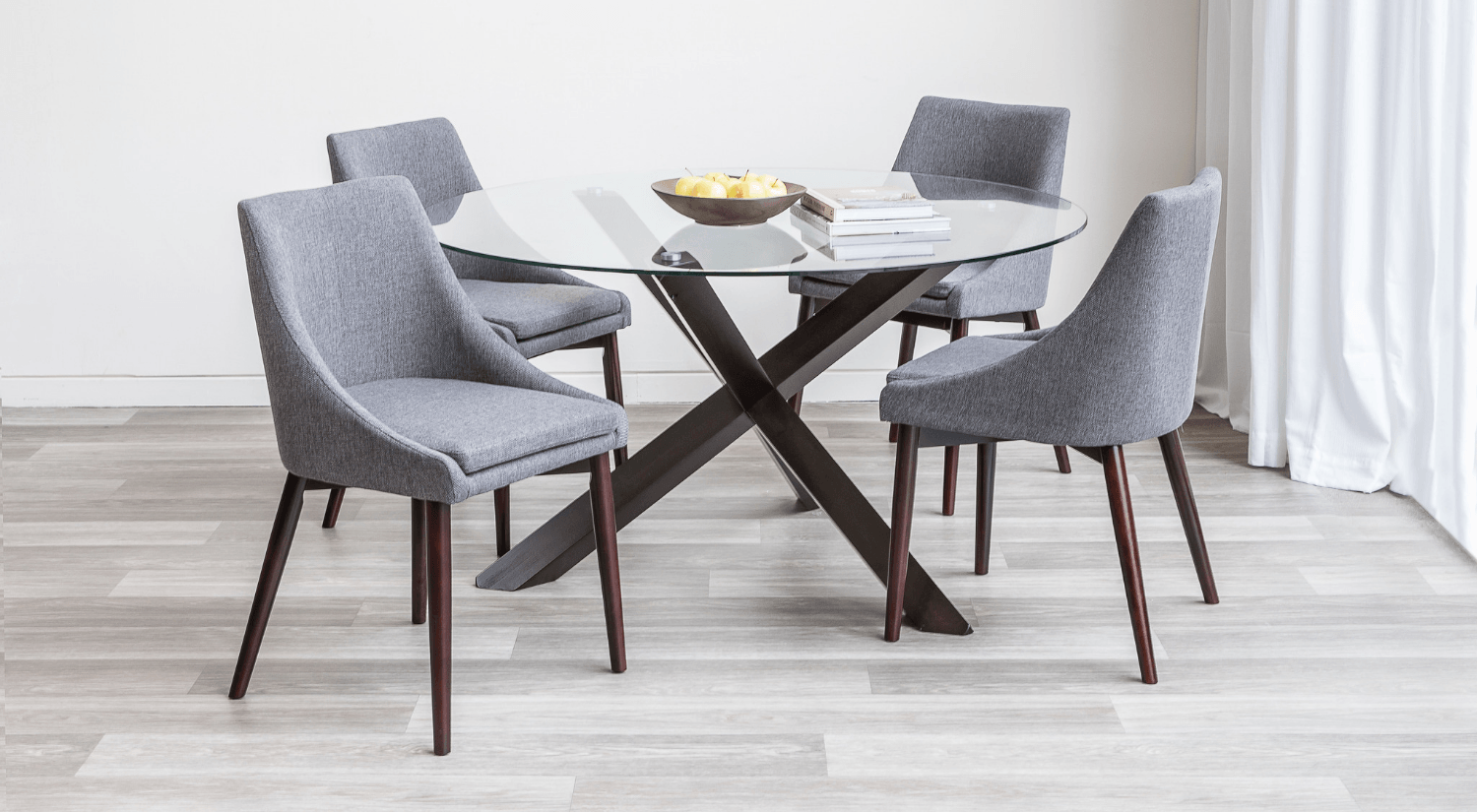 Circular glass dining room table with four grey fabric chairs.