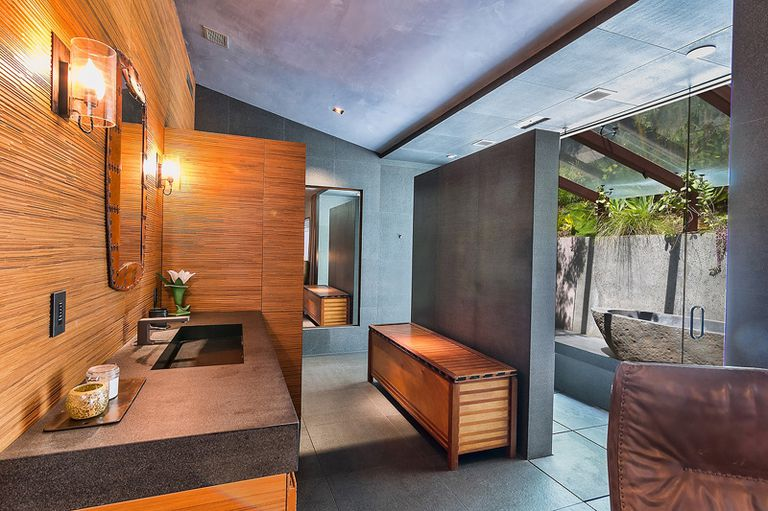 Bathroom with wood paneling, concrete details and outdoor tub.