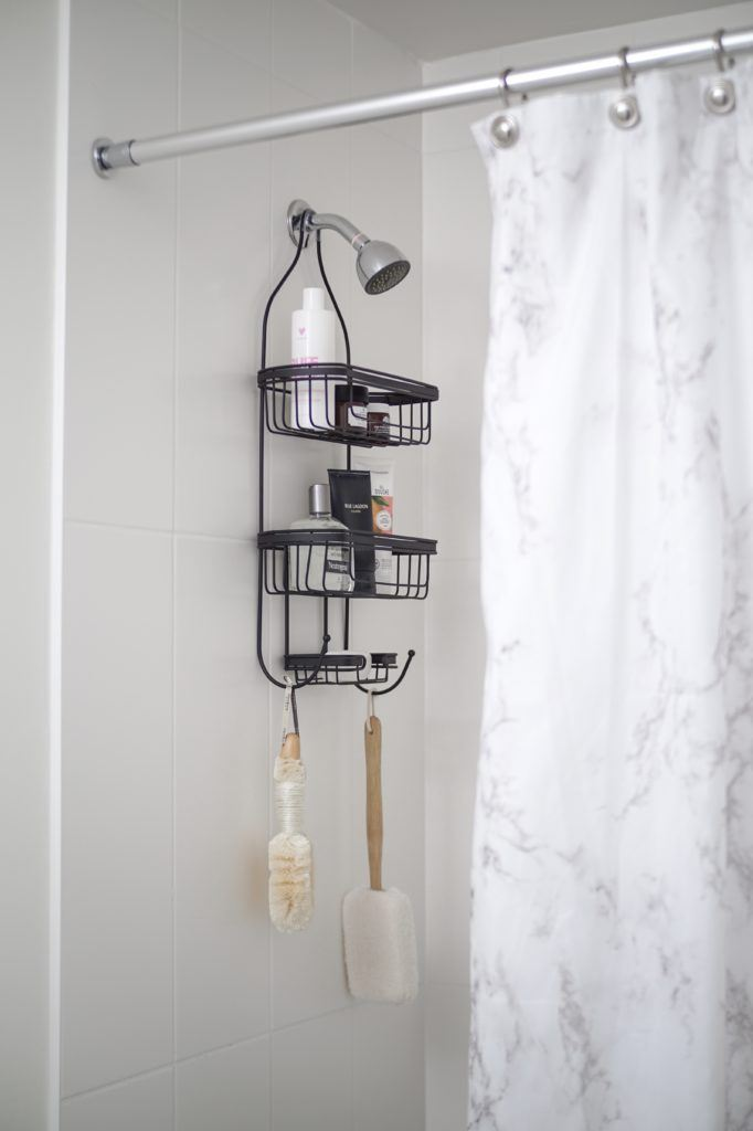 black shower caddy hanging from shower head with bottles on the shelves and brushes hanging