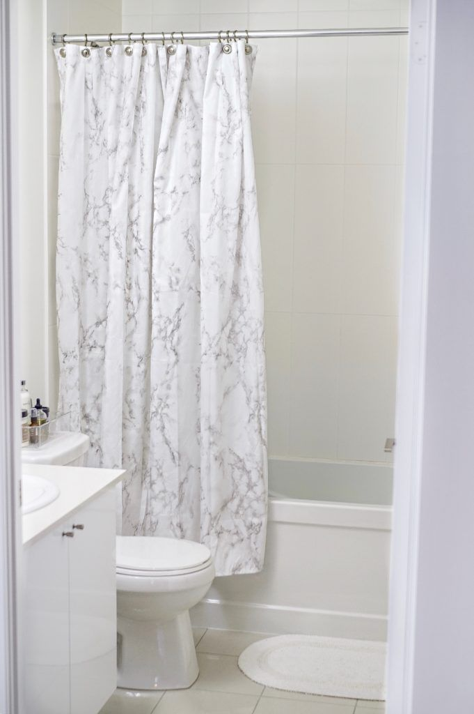 white marble shower curtain half open over a shower/bathtub combo
