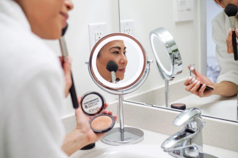 reflection in mirror of woman putting on makeup