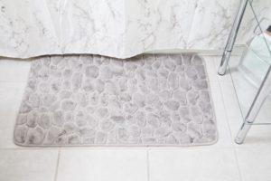 grey bathmat outside a bathtub