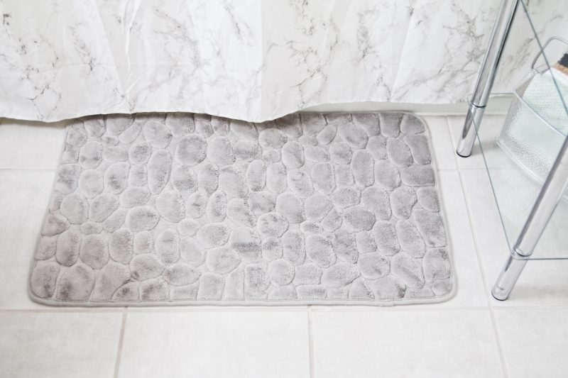 grey bathmat outside a bathtub