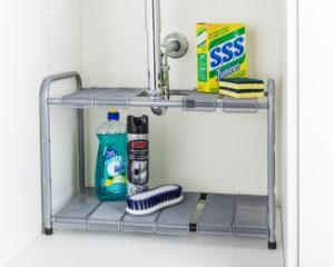 under the sink storage shelf with cleaning products.