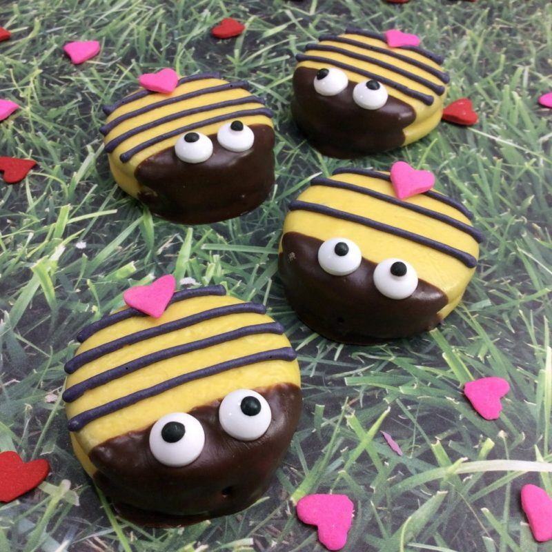 Oreos covered in yellow melted chocolate and decorated with black icing stripes and candy eyes to make a bumblebee.