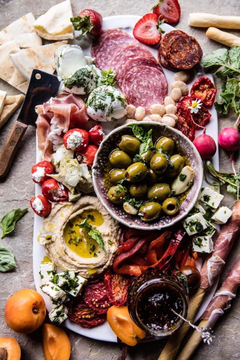 charcuterie board with meats, cheese, olives, jams, breadsticks