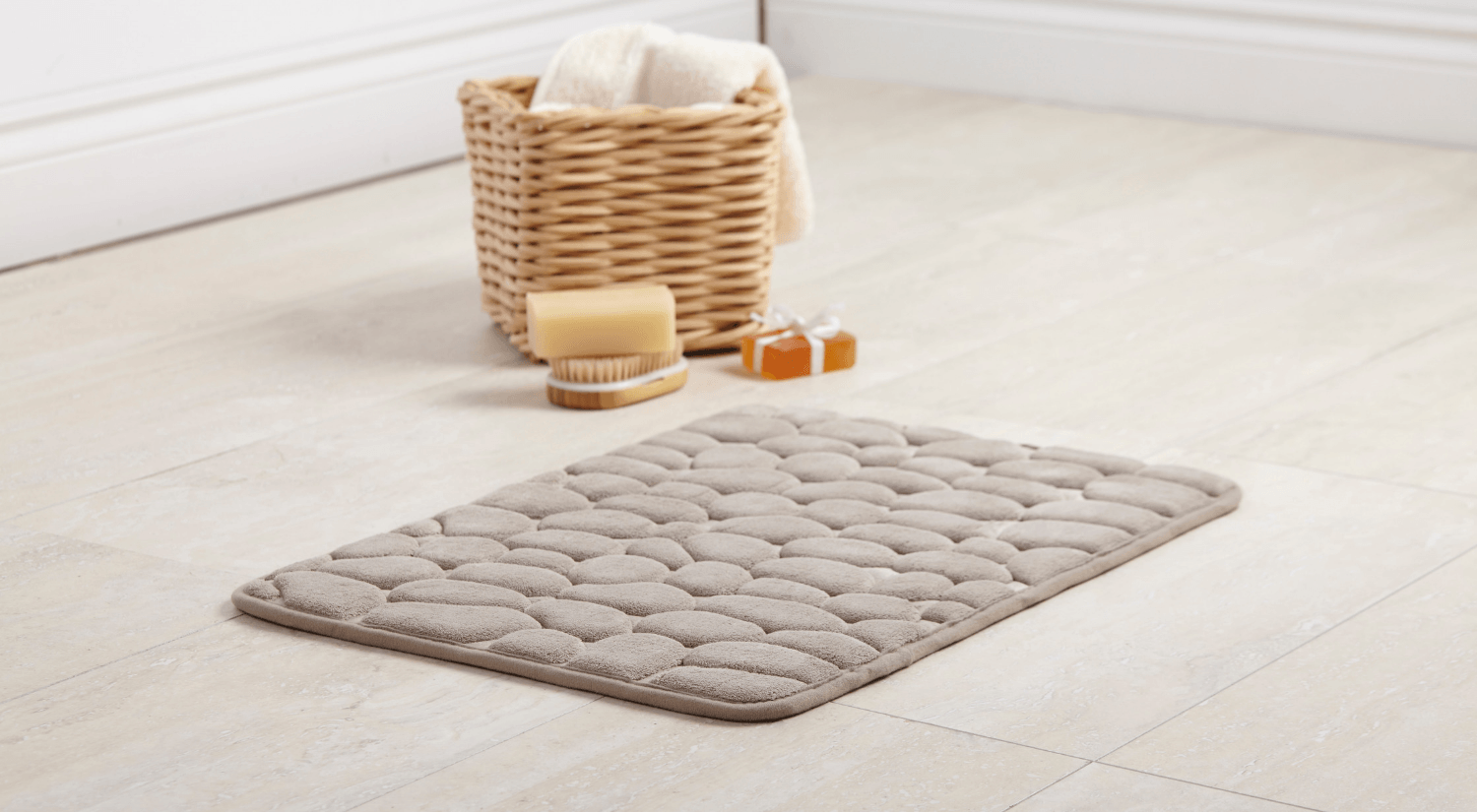 grey bathmat with stone design and wooden basket filled with bath accessories