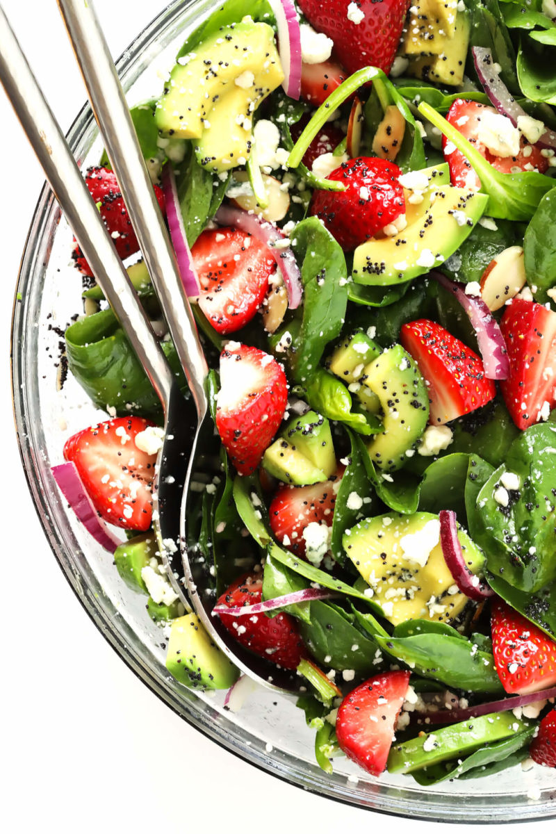 spinach, strawberries, and avocado drizzled in a poppyseed dressing in a salad bowl