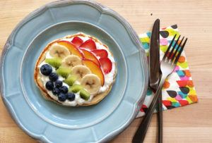 Blue plate with a pancake topped with greek yogurt, blueberries, kiwi, bananas, peaches and strawberries to make a fruit rainbow.
