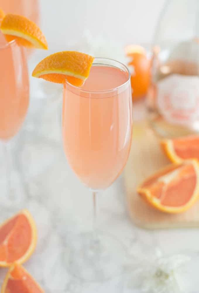 grapefruit mimosa in a champagne glass with a wedge or orange