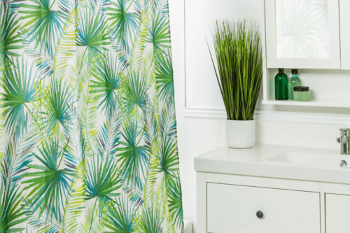 palm tree shower curtain half open in a shower
