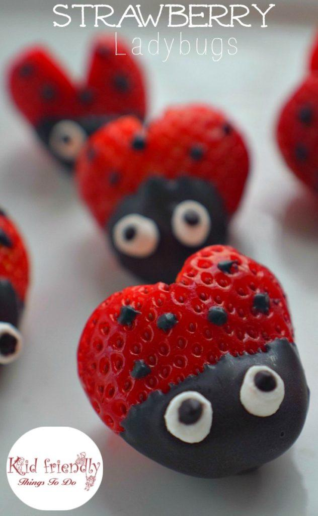Strawberries cut into heart shapes, partially dipped in chocolate and decorated with dark chocolate spots and candy eyes to make a ladybug.