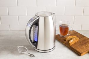 stainless steel kettle beside a cup of tea, cookies, and tea diffuser