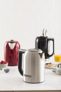 three kitchenaid kettles in silver, red, and black