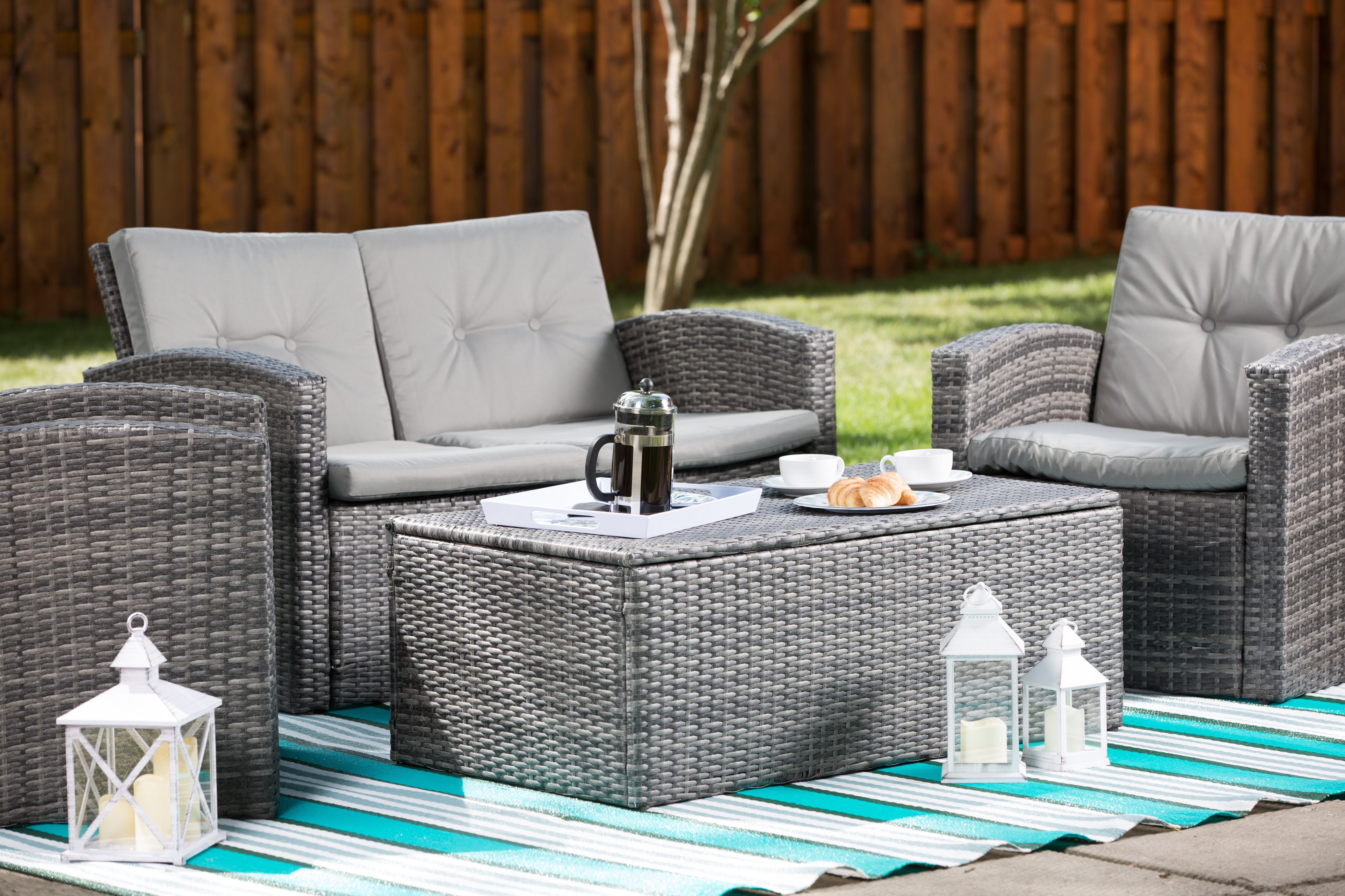 Set of 4 grey outdoor patio set with one love seat, two single seaters, coffee table, lanterns and blue outdoor mat