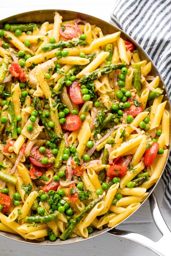 pasta in a pan with pea, tomatoes, asparagus, and other spring vegetables