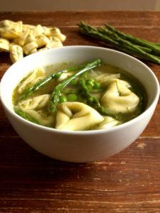 a bowl of soup with tortellini, peas, and asparagus