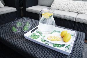 a pitcher of lemon water and a leaf shaped plate with lemons on the tropico serve tray, glasses with a leaf beside the tray
