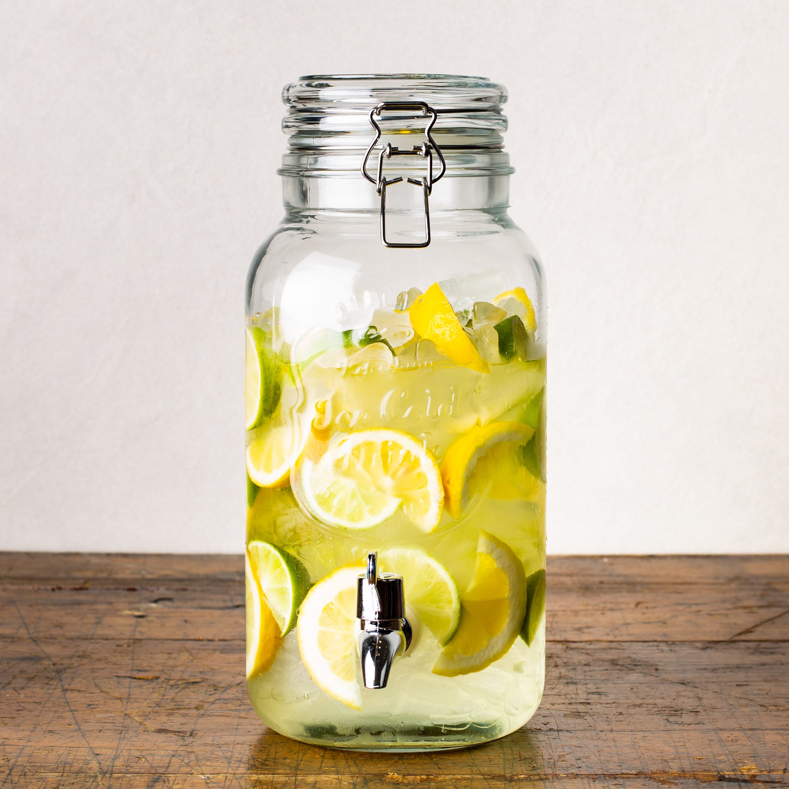 glass beverage dispenser with ice, limes, and lemons