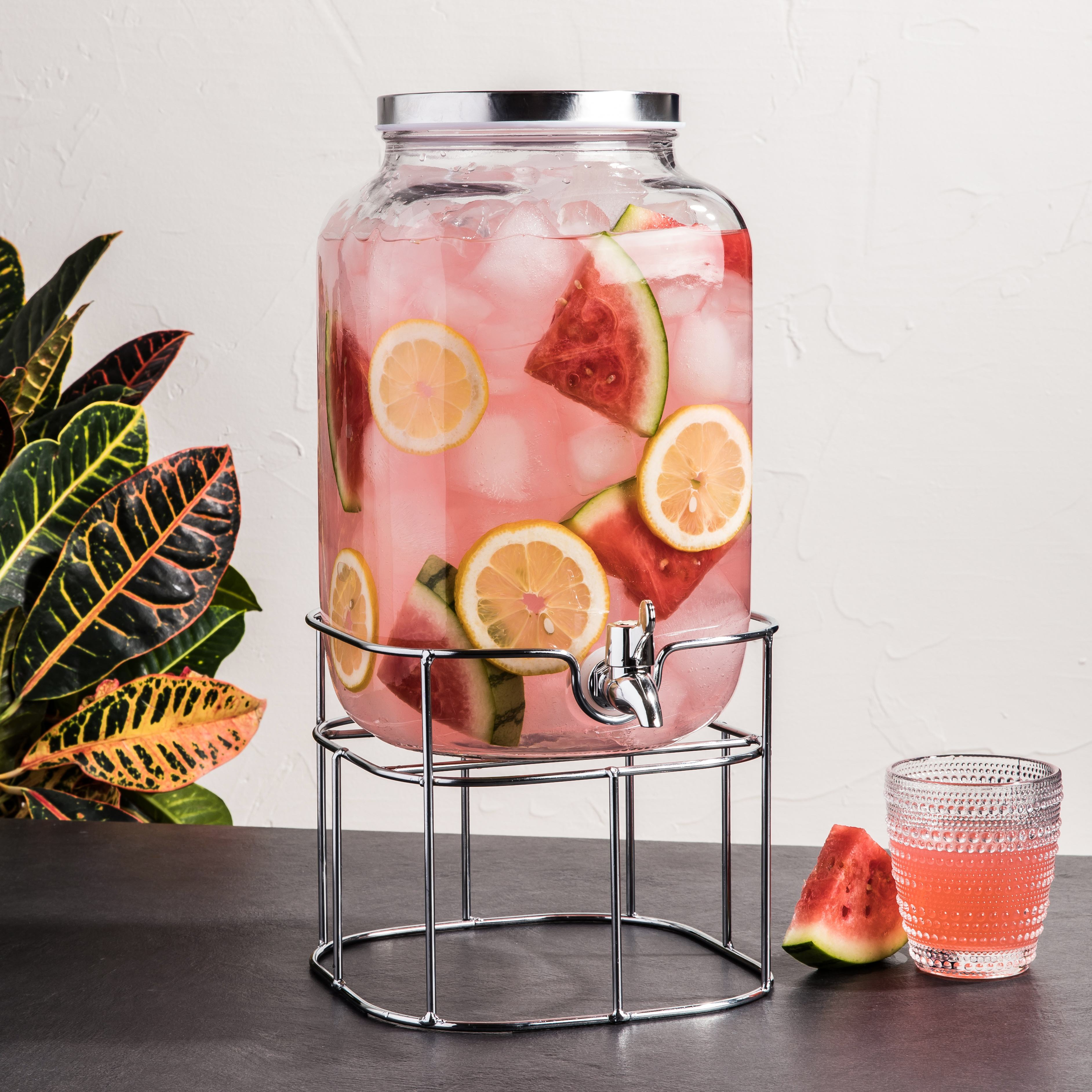 glass beverage dispenser fill with water, ice, lemon, and watermelon on a stand