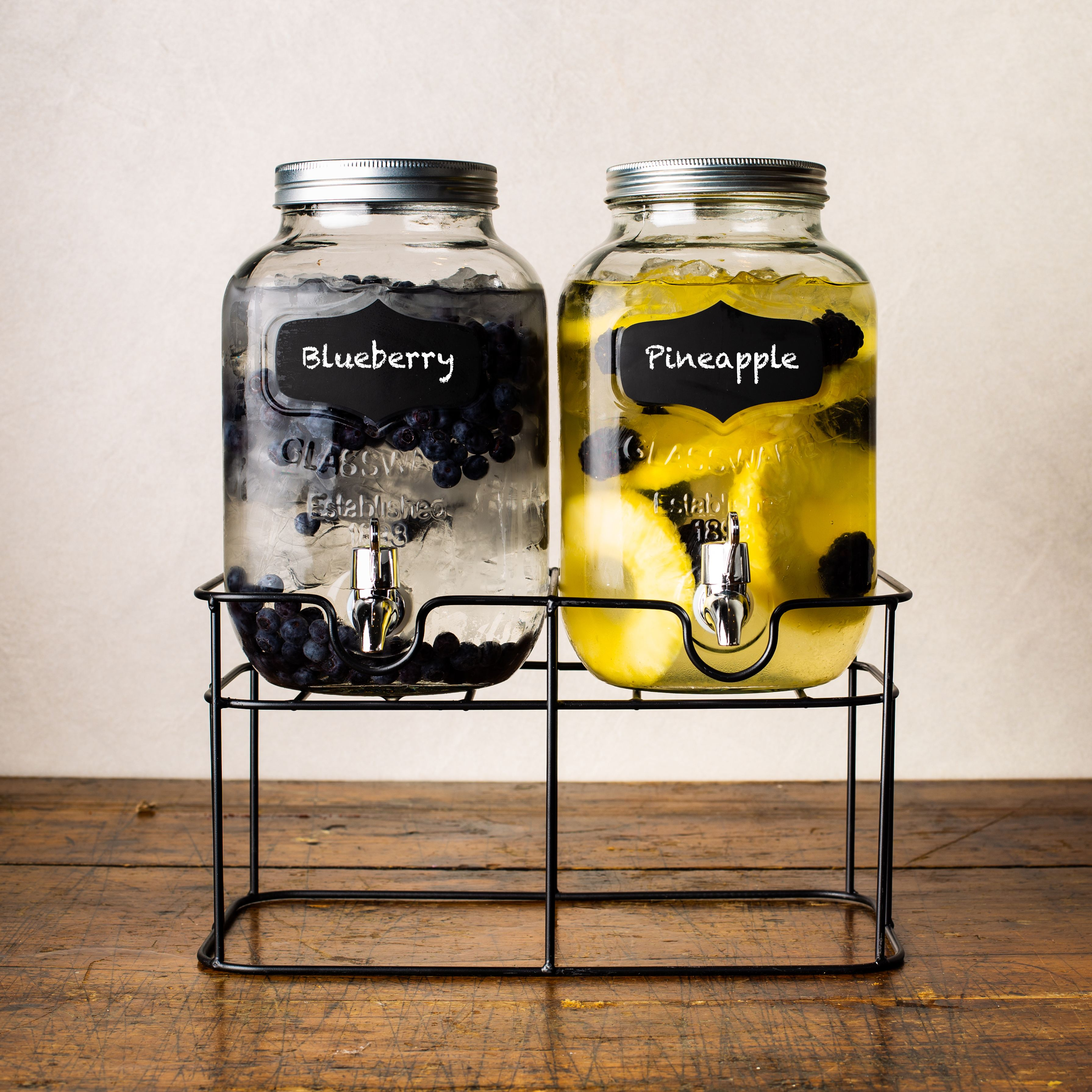 a set of two glass beverage dispensers with chalkboard labels on a stand, one dispenser filled with water, ice, and blueberries, the other filled with water, pineapple, and blackberries