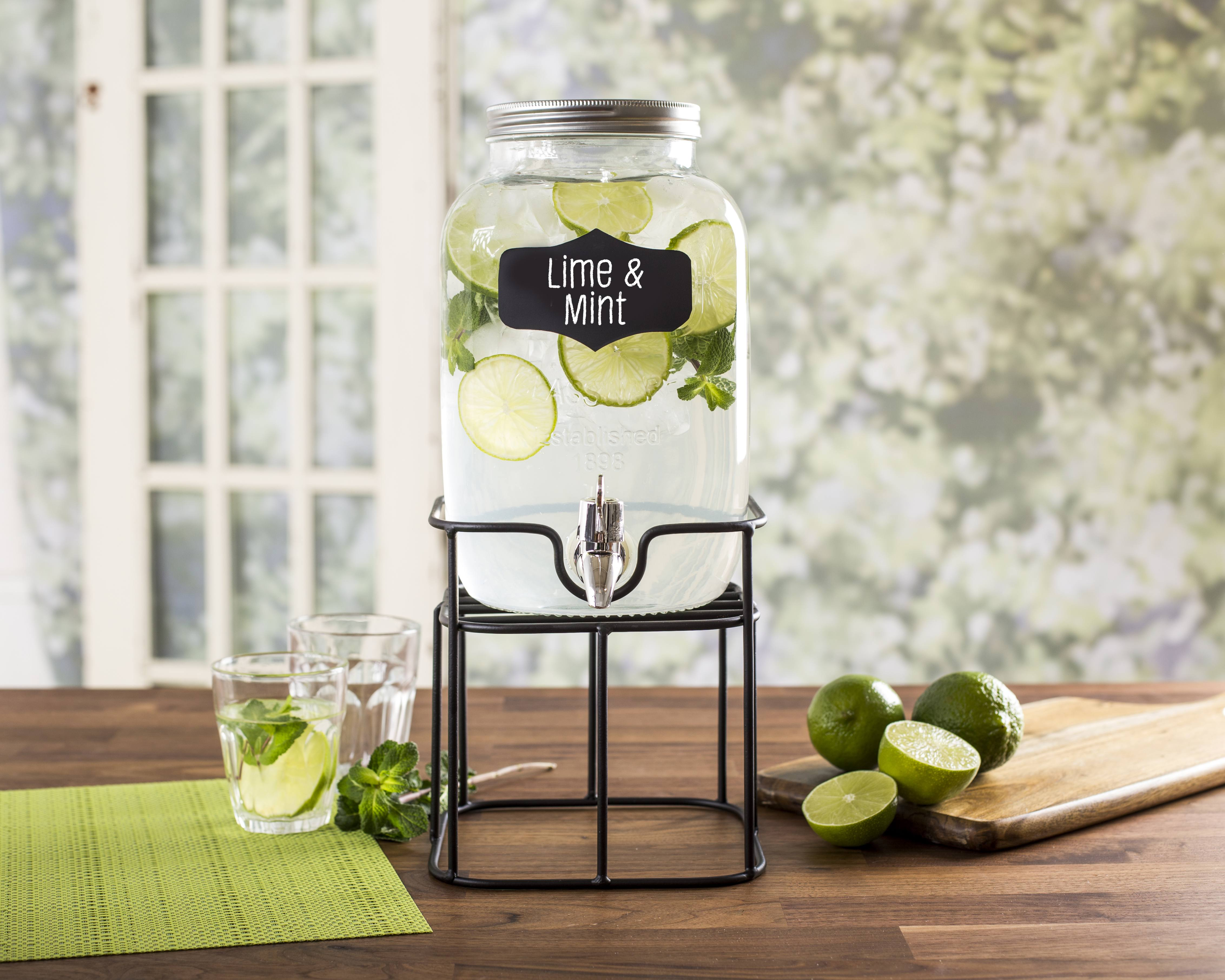 glass beverage dispenser with chalkboard tag on a stand, filled with water, ice, limes, and mint