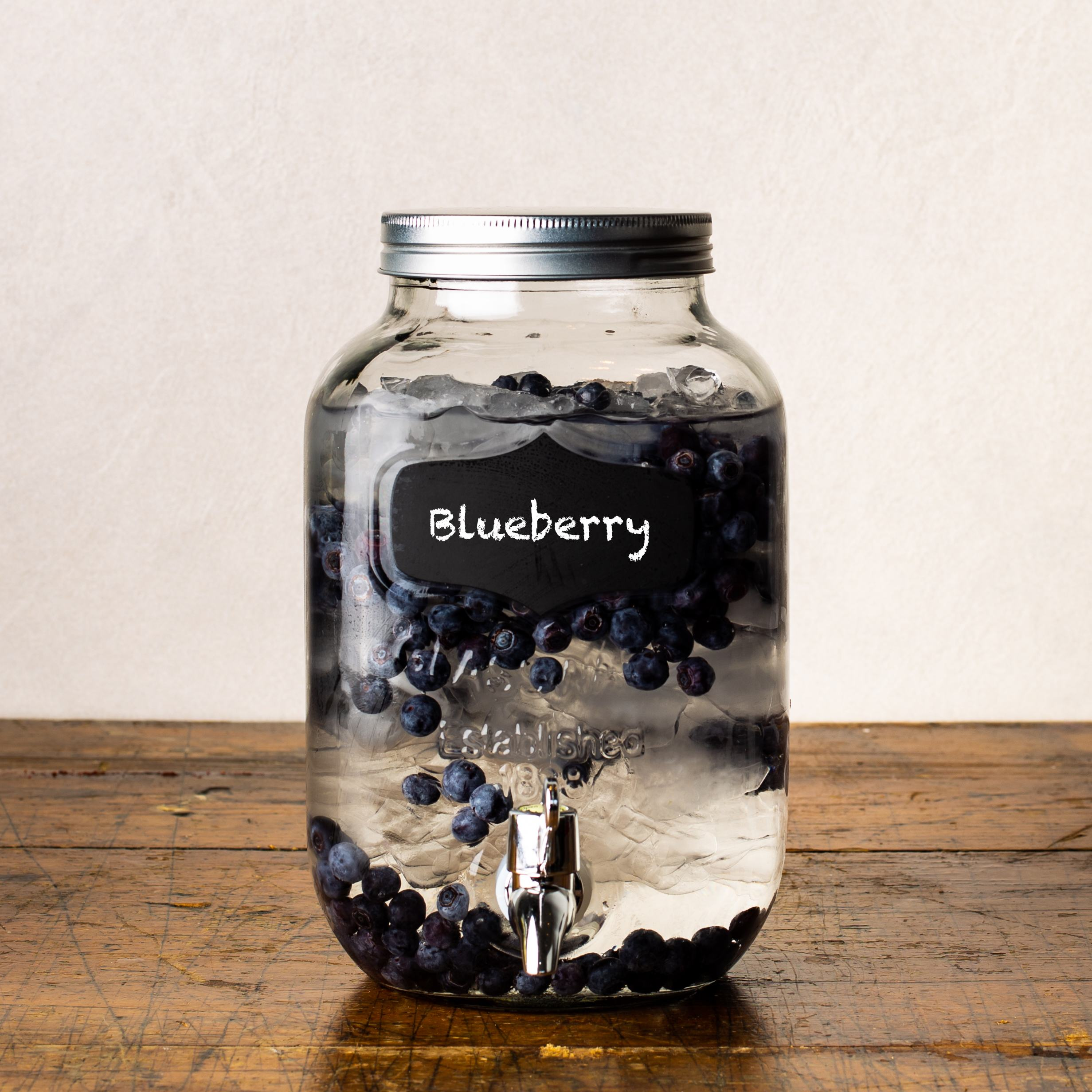 glass beverage dispenser with chalkboard tag, filled with water, ice, and blueberries