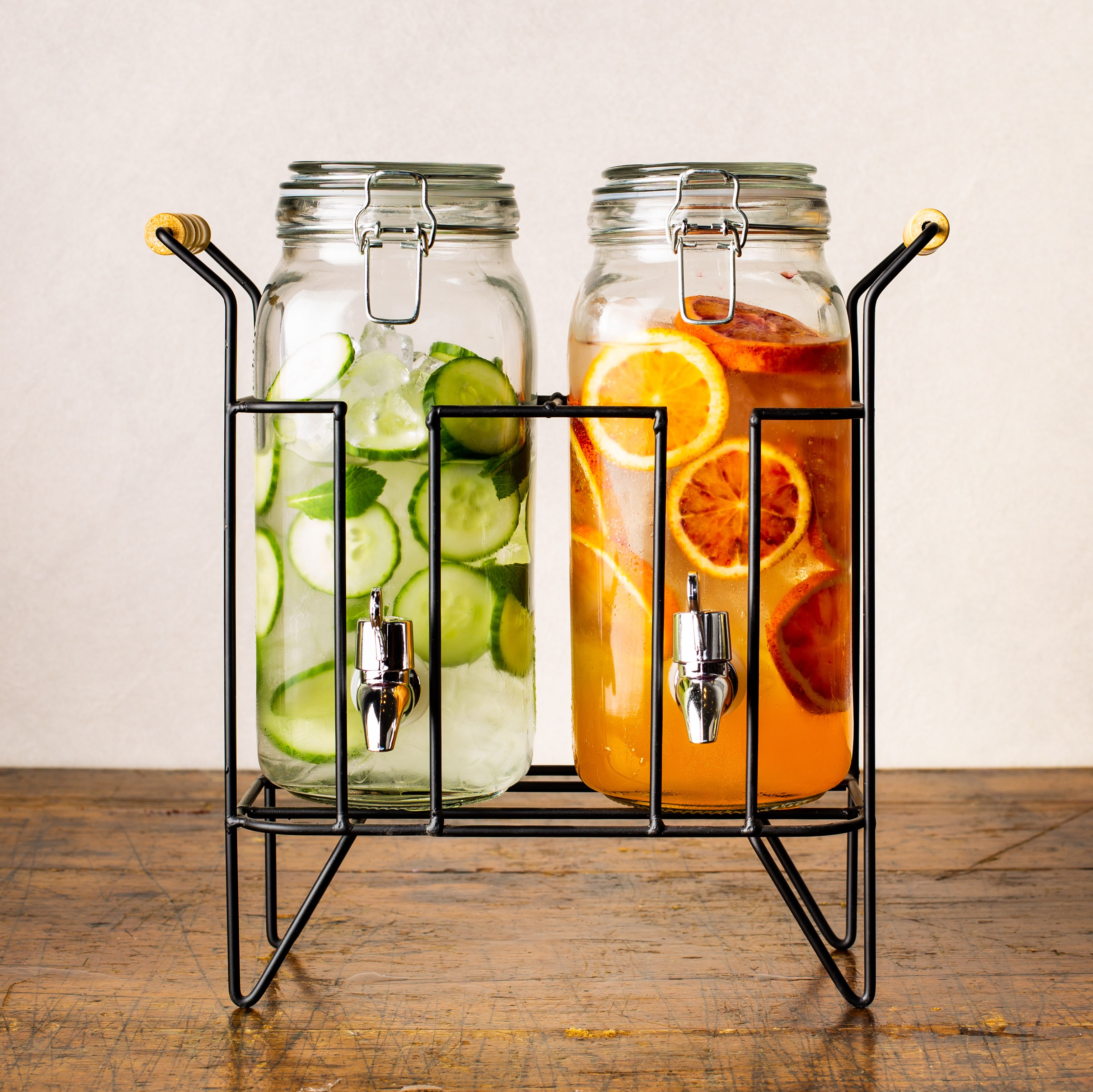 a set of two glass beverage dispenser on a stand, one dispenser filled with water, ice, cucumber, and mint, the other filled with juice and oranges