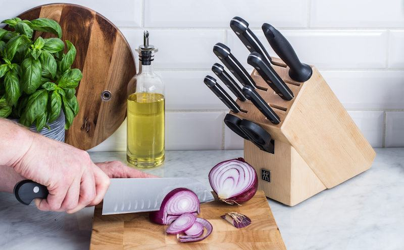henckels knife block and person chopping an onion with a chef knife