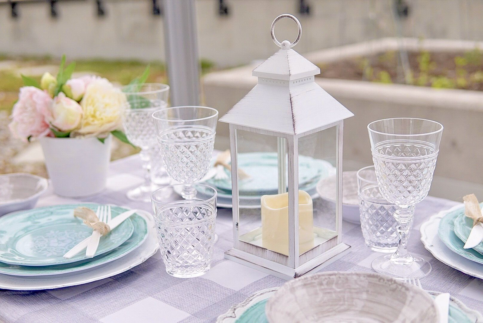 white metal lantern on a table with melamine dinnerware